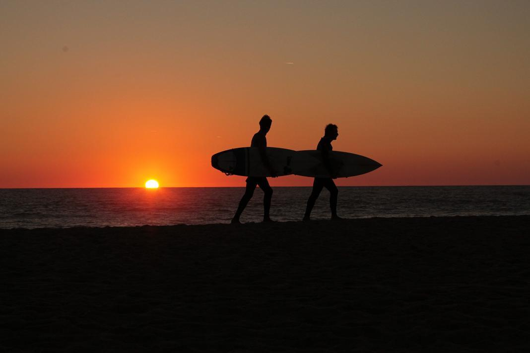A photo of surfers in the sunset by Sean Keenan